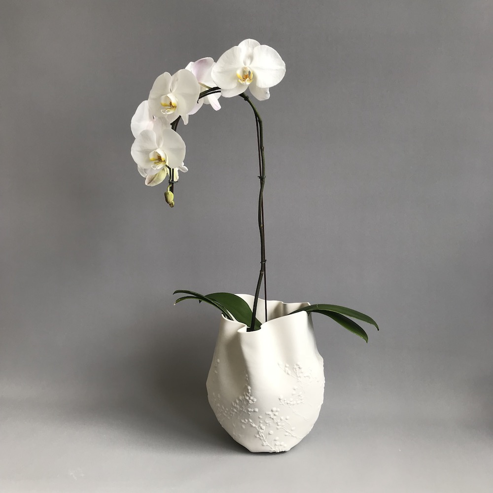 white soft pot with orchid